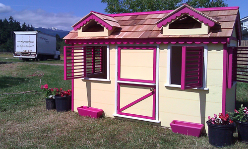 Yellow and pink wooden playhouse